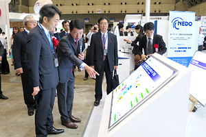 photo: Parliamentary Vice-Minister of Economy, Trade and Industry Toshinao Nakagawa visiting the NEDO booth (left)