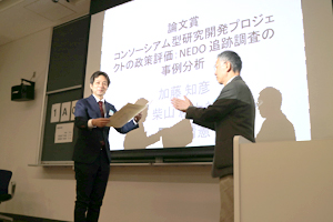 photo: Technology Strategy Center researcher Dr. Tomohiko Kato receiving the best paper award