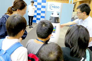 NEDO staff giving an explanation of exhibited robot at the presentation space