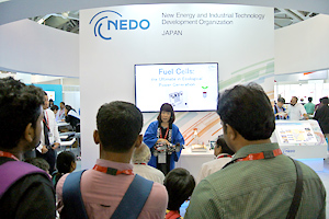 Many visitors observing NEDO's presentation at the booth