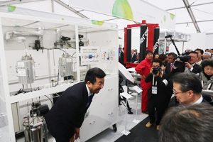 Photo of Minister of Economy, Trade and Industry, Mr. Hiroshige Seko, visiting Hitachi Zosen Corporation's exhibit of technology converting CO2 and hydrogen into methane