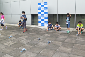 Photo of children testing solar cars outside event venue