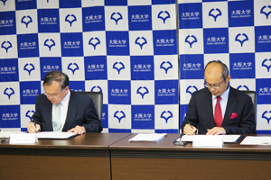 Photo of NEDO Executive Director Masayoshi Watanabe and Dr. Yasufumi Kaneda, Senior Executive Vice President of Osaka University, signing MOC