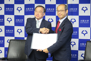 Photo of Executive Director Watanabe and Senior Executive Vice President Kaneda displaying signed MOC