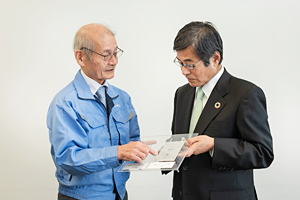 Photo of Dr. Yoshino and Chairman Ishizuka exchanging views regarding all-solid-state lithium-ion battery