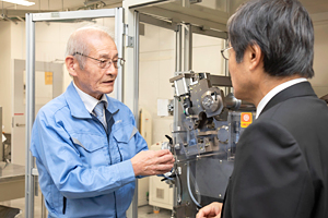 Photo of Dr. Yoshino explaining production process for conventional lithium-ion battery